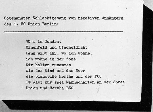 """""""Chants de guerre entonnés par les supporters négatifs du 1. FC Union Berlin : """"30m², champ de mines et Rideau de Fer, vous savez donc où j'habite, j'habite dans la Zone"""" - """"Nous nous dressons ensemble, comme le vent et la mer, le Hertha BSC bleu et blanc, et le FCU"""", """"Il n'y a que deux équipes sur les bords de la Spree : l'Union et le Hertha BSC"""""""" (traductions de l'auteur, (c) Archives de la Stasi)"""